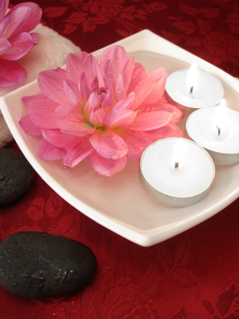 Spa essentials (candles, flowers on water, towel and stones)